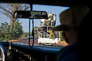 Mopti, Mali 2009 -  View from inside a taxi on the road from Sévaré to Mopti. A pickup truck, acting as a traditional group taxi, loaded with people and cargo fills the road in front of us.