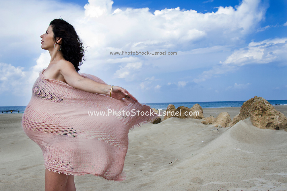 Pregnant woman on the beach with flowing fabric