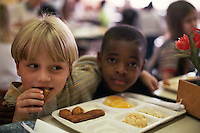 May 1998, Asheville, North Carolina, USA --- First grader Tunui Franken hugs classmate Robert McClendon as they eat their school lunches at the Claxton Elementary School cafeteria. --- Image by © Owen Franken/CORBIS