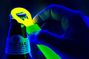 A bottle of beer being opened with a glowing bottle operner.  Blacklight photography.