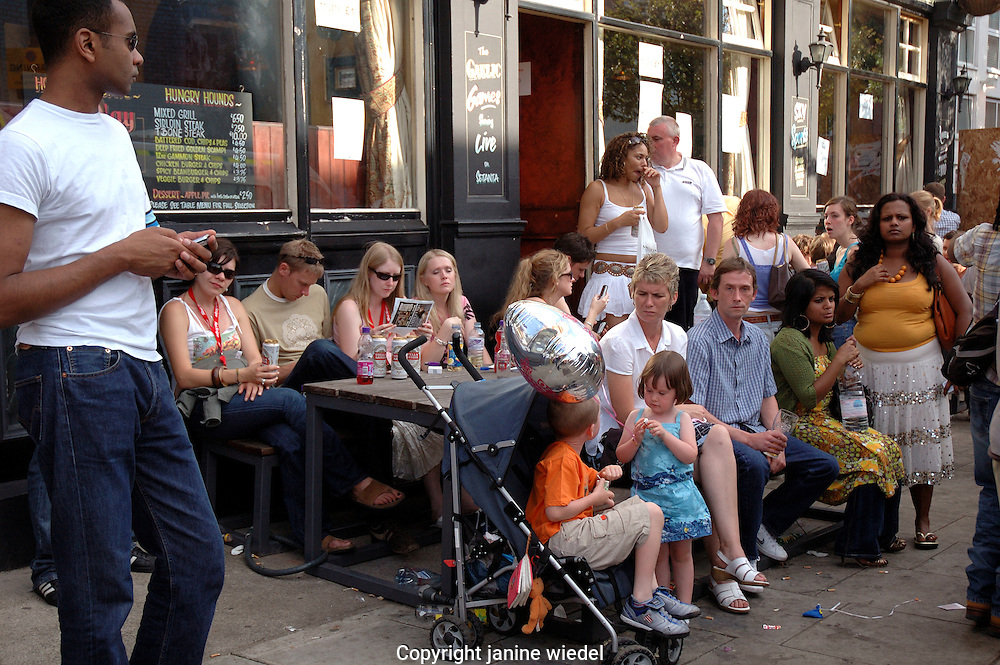 Multi-cultural group of people sitting outside pub drinking and relaxing in summer.