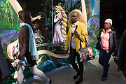Disney character Rapunzel from their film Tangled stands looking at women, exemplifying feminine beauty. A smaller than life-size model of the Disney character Rapunzel from their company's film called Tangled stands in the window of their London store, seemingly looking out in admiration and delight at a young woman with similarly coloured hair and carrying a Marylin Monroe printed bag. Advertising the forthcoming opening of the movie, the display of the central character exemplifies feminine health, beauty, and inadvertently, of American or white European values. The woman walks past oblivious at the attention that this fictitious person is affording them – her own lifestyle being an everyday personal choice of style and a statement about femininity and gender on this urban street.