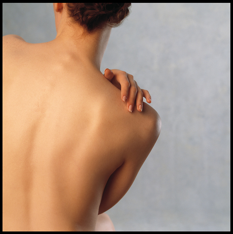 Skincare photo of nude woman's flawless back with hand on shoulder