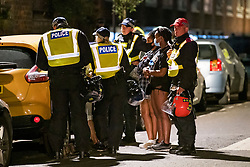 © Licensed to London News Pictures. 26/06/2020. London, UK. Police in riot equipment talk to a group of women as they attempt to disperse an illegal Street Party at Riverton Close in Maida Vale, West London.  A number of similar events have occurred across the capital, with some resulting in violence towards police. Photo credit: Ben Cawthra/LNP