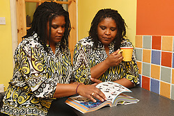 Identical twins looking at a catalogue.