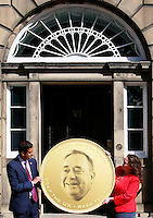 Scottish Labour deputy leader Anas Sarwar and credit union leader worker Alison Dowling holding a gigant coin to deliver to the Bute House in Charlotte Square. Edinburgh.<br /> Scottish Labour deputy leader Anas Sarwar and credit union leader worker Alison Dowling deliver a giant pound coin to Bute House. The First Minister's official residence, to highlight uncertainty over what currency an independent Scotland would use.<br /> <br /> Pako Mera/Universal News And Sport (Europe) 07/08/2014
