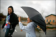 """Lupita Hernandez and her daughter, Ivanna, laugh in the rain as they leave the National Dance Institute of New Mexico. At the time of this photo in March, immigration raids and arrests in Santa Fe had made many undocumented immigrants uneasy. """"I don't want them to take my mom away from me,"""" said Ivanna, who is a U.S. citizen."""
