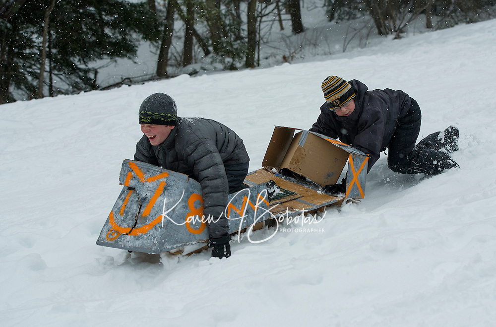 Mark Young and James Buckley have a cardboard meltdown with their #8 sled in the wet sticky snow Wednesday morning during the annual Cardboard Derby with Gilford Parks and Recreation at the Outing Club Hill.  (Karen Bobotas/for the Laconia Daily Sun)