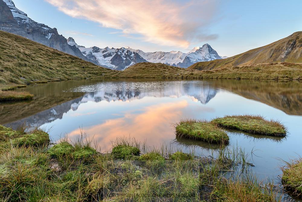 Spiegelung der Berner Hochalpen mit Mönch (4107) und Eiger (3970) in einem Bergsee beim Gummi oberhalb der Grossen Scheidegg bei Grindelwald an einem schönen Herbstmorgen im Oktober.