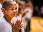 15 MARCH 2015 - SIEM REAP, SIEM REAP, CAMBODIA: Women pray at the annual mass merit making at Wat Bo in Siem Reap. More than 1,200 Buddhist monks, from across Siem Reap province, received alms from Buddhist lay people during the morning long ceremony. Wat Bo was originally built to be a the temple for Siamese (Thai) troops when Siem Reap and western Cambodia were controlled by Siam (Thailand). Now Wat Bo is one of the most important temples in Siem Reap.      PHOTO BY JACK KURTZ