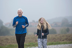 Father with his daughter jogging on footpath and smiling during dawn, Bavaria, Germany