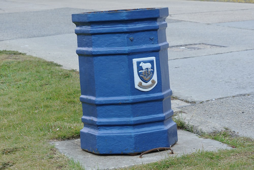 Blue rubbish bin on a roadside in Stanley. The Falkland Islands coat of arms and motto 'Desire the Right' are on the bin.