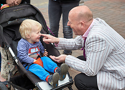© Licensed to London News Pictures.  30/04/2015. AYLESBURY, UK. Chris Adams, UKIP candidate for Aylesbury, talks to a young boy ahead of a visit by party leader Nigel Farage (not seen).  Photo credit: Cliff Hide/LNP