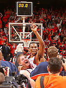 Virginia basketball players Sean Singletray, right, and Lars Mikaluaskas, left, are surrounded by media after stunning nationally ranked Arizona during their season opener in Charlottesville, Va.