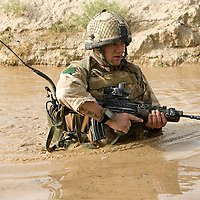British soldiers of 3rd Battalion The Parachute Regiment wade through filthy water filled irrigation ditches whist on a desert patrol after an airborne assault as part of Operation 'Southern Beast'. Kandahar Province, Afghanistan on the 4th of August 2008.