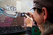 Irina Gendelman takes updated photos of graffiti in an alley in the University District of Seattle, Washington on October 18, 2006. The piece had been partially buffed, or repainted. Gendelman, a Communications graduate student at the University of Washington, co-founded Urban Archives, an image database of urban communication from cities around the world whose main mission is to record urban texts, like graffiti, public art and signage, that can quickly disappear. Gendelman has focused her research on political graffiti and the policy issues surrounding this controversial art form.