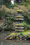 The moss covered Kaisekito Pagoda next to the Hisagoike Pond in the Kenrokuen Garden, Kanazawa, Ishigawa, Japan
