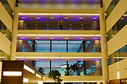 "A guest looks out from a walkway down on to a  wide atrium within Sofitel, a 605 bedroom, 27 suite and 45 meeting room accommodation and business hub, situated at Heathrow Airport 's Terminal 5 hotel. Large areas of glass make this a landscape of modernity and the last daylight mixes with artificial lighting from the atrium's spotlights.From writer Alain de Botton's book project ""A Week at the Airport: A Heathrow Diary"" (2009). ..."