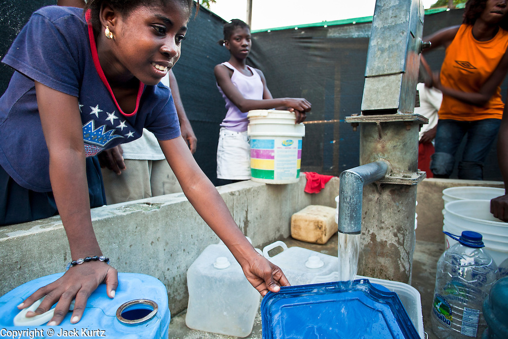 17 NOVEMBER 2010 - LEOGANE, HAITI: A woman fills her water bucket at a public well in Leogane. The water from the well is not fit for human consumption but, other than a nearby waste canal, is the only source of water in the community. An outbreak of cholera in northern Haiti about a month ago has spread across the nation. Tens of thousands of people have been hospitalized and treated for cholera and more than 1,100 have died. Cholera is a water borne illness that causes severe diarrhea and death by dehydration in a matter of hours.  PHOTO BY JACK KURTZ  choleraepidemic