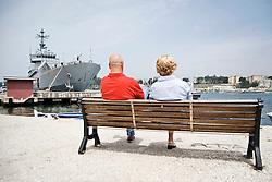 Una coppia seduta in riva al mare al porto di Brindisi con sullo sfondo una nave da guerra ancorata. 29/05/2010 PH Gabriele Spedicato