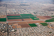 SHOT 1/28/15 10:47:20 AM - Agricultural fields amongst the sprawl in Phoenix, Arizona. Phoenix is the capital, and largest city, of the state of Arizona. With 1,445,632 people (as of the 2010 U.S. Census), Phoenix is the most populous state capital in the United States, as well as the sixth most populous city nationwide. Located in the northeastern reaches of the Sonoran Desert, Phoenix has a subtropical desert climate. Despite this, its canal system led to a thriving farming community, many of the original crops remaining important parts of the Phoenix economy for decades, such as alfalfa, cotton, citrus and hay (which was important for the cattle industry). (Photo by Marc Piscotty / © 2015)