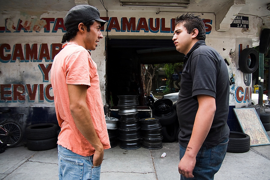 Rodrigo Canavas, left, director of Azoteas Verdes (Green Roofs), convinces a mechanic to let him collect used car tires from his shop in Mexico City, Mexico on June 17, 2008. The organization promotes roof garden construction throughout the city, teaching workshops, collecting used containers and preparing compost from organic waste.