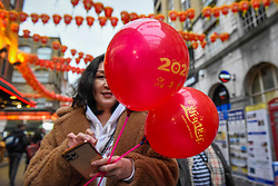 © Licensed to London News Pictures. 24/01/2020. LONDON, UK. A woman carries red balloons as red lanterns decorate Chinatown ahead of Chinese New Year, the Year of the Rat.   Photo credit: Stephen Chung/LNP