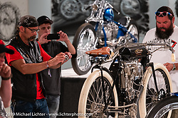 """Guests check out the 1908 Indian Twin """"Torpedo Tank"""" 61 cubic inch board track racer from the Jill and John Parham Collection at the National Motorcycle Museum on view in the What's the Skinny Exhibition (2019 iteration of the Motorcycles as Art annual series) at the Sturgis Buffalo Chip during the Sturgis Black Hills Motorcycle Rally. SD, USA. Thursday, August 8, 2019. Photography ©2019 Michael Lichter."""