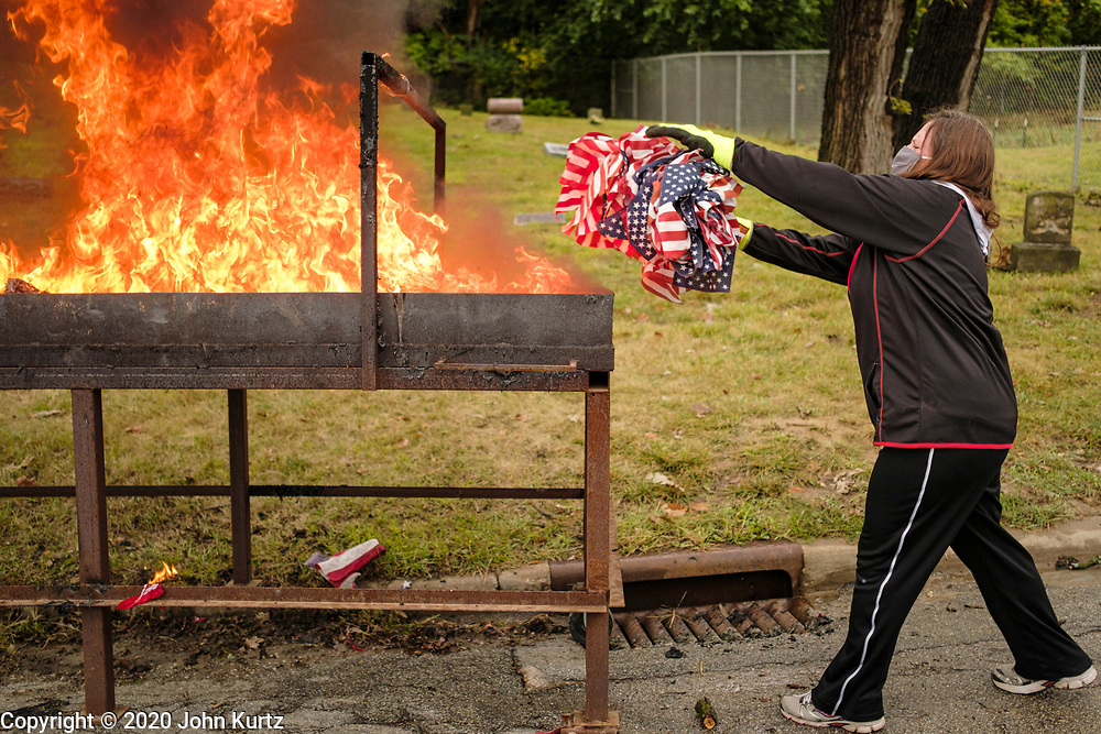 12 SEPTEMBER 2020 - DES MOINES, IOWA: DIXIE EVANS throws a bundle of US flags into a fire during a flag retirement ceremony at Glendale Cemetery in Des Moines. About 10 volunteers came to the cemetery Saturday morning to properly dispose of about 4,000 American flags. The flags had flown over veterans' graves, local businesses, and state offices. The US Flag Code calls for used American flags to be respectfully disposed of in a fire.    PHOTO BY JACK KURTZ
