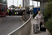 As environmental activists protest about Climate Change during the occupation of City Airport Londons Business Travel hub in east London, a recently-arrived passenger tries to find transport away from the blockade on the fourth day of a two-week prolonged worldwide protest by members of Extinction Rebellion, on 10th October 2019, in London, England.