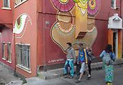 Pedestrians walk past a building covered in street art. Cerro Alegre, Valparaiso.