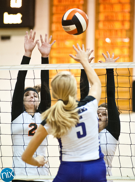 Northwest Cabarrus' Savannah Cox (2) and Katy Gaudet (5) go up to block a shot by Cox Mill's Alison Hollis (5) Tuesday night at Northwest Cabarrus High School. The Trojans won in four games. (Photo by James Nix)