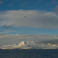 Mountains on Anvers Island glow in a sunset above Gerlache Strait.