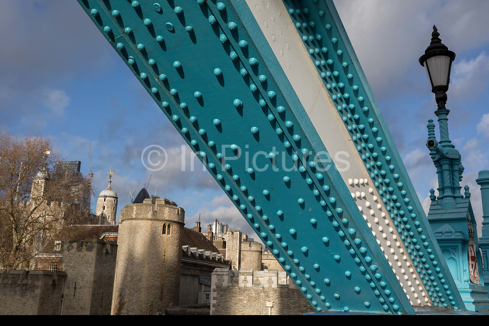 The Tower of London in the distance with the steel rivets from one of Tower Bridges steel suspension anchor girders, on 14th December 2017, in the City of London, England.
