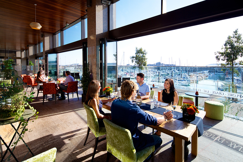 People enjoying drinks and socialising at the restaurant Tiffin overlooking the waterfront and Elizabeth Marina in Jersey, Channel Islands