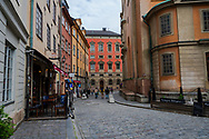 Stockholm, Sweden -- July 16, 2019. Some tourists walk past shops and a restaurant on a circular street in Old Town, Stockholm.