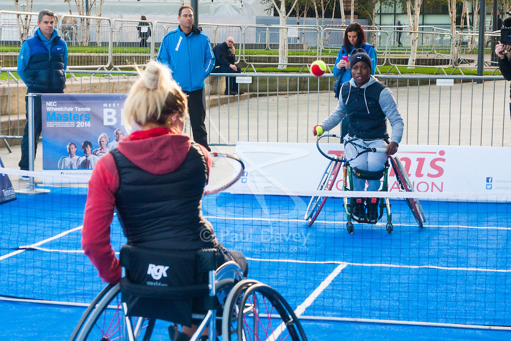 City Hall, London, November 24th 2014. Mayor Boris Johnsonwelcomes the world's best wheelchair tennis players with a game of mini tennis outside City Hall. The players are in London to compete in the NEC Wheelchair Tennis Masters 2014, being held at the Lee Valley Hockey and Tennis Centre, being held from 26 - 30 November. PICTURED: Great Britain's Jordanne Whiley and South Africa's Kgothatso Montjane enjoy a knockabout in front of City Hall.