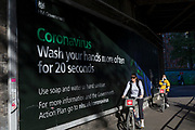 As the number of new Coronavirus cases in the UK climbs to 201,101, with UK deaths now standing at 30,076 - the highest recorded in Europe, <br /> a Londoner carrying toilet rolls walks beneath a government billboard advising the public on viral hygiene during the continuing Covid lockdown, on 6th May 2020, in south London, England.