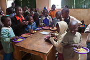 Plates of freshly cooked food are given out by the kitchen staff to the pupils at Kibera School, Nairobi. The school consists of 6 teachers with approximately 60 children in each class.  Undugu Society of Kenya (USK), an NGO who run various programmes to help the school and pupils including a lunchtime feeding program.