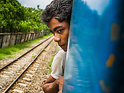 05 JUNE 2014 - YANGON, YANGON REGION, MYANMAR: A passenger of the Yangon Circular Train. The Yangon Circular Train is a commuter train that circles Yangon, Myanmar (Rangoon, Burma). The train is 45 kilometers long, makes 38 stops and takes about three hours to make a loop of the city.     PHOTO BY JACK KURTZ