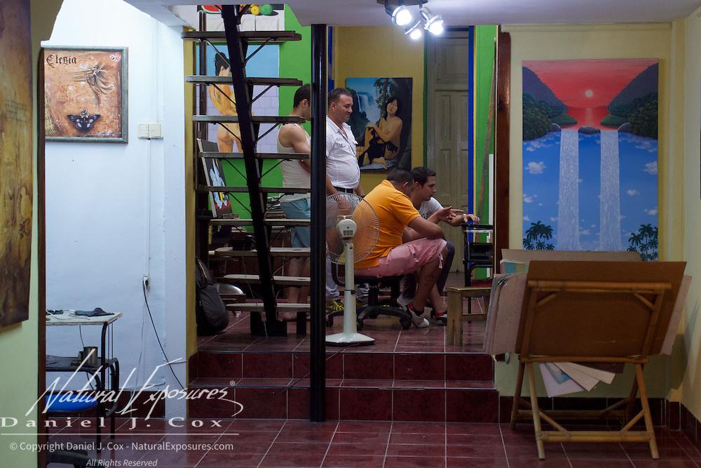 Local Cubans at an art gallery looking at art on a computer screen, Havana, Cuba