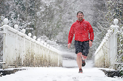 © Licensed to London News Pictures. 12/04/2021. Elstree, UK. A runner braves the snow on Reigate Hill in Surrey as early morning flurries hit the south. Photo credit: LNP