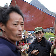 A group of men smoking at the Lung Khau Nhin Market. Vietnam. Lung Khau Nhin Market is rural tribal market hiding itself amongst the mountains and forests of the far north Vietnam about 10 km from the border with China. The market plays an important role for the local ethnic people, Flower Hmong, Black Zao, Zay, and very small ethnic groups  Pa Zi, Tou Zi, Tou Lao. Tourist trips to the market run from Sapa and Lao Cai every week. Lung Khau Nhin Market, Vietnam.15th March 2012. Photo Tim Clayton