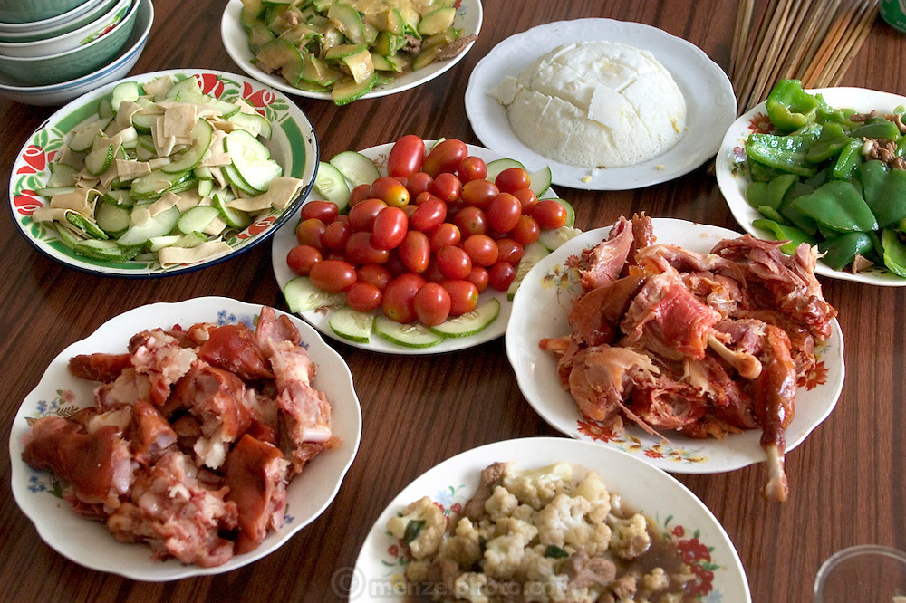 The Cui family lunch always includes rice and vegetables fresh from the garden like tomatoes and squash, but also includes chicken, pigs' feet, beef, tofu, and egg-white custard. Weitaiwu Village, China. (From a photographic gallery of meals in Hungry Planet: What the World Eats, p. 244). The Cui family of Weitaiwu village, Beijing Province, China, is one of the thirty families featured, with a weeks' worth of food, in the book Hungry Planet: What the World Eats.