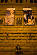 A young Italian woman sits on a ledge outside the Piazza Strozzi in central Renaissance city of Florence. Above her are giant posters advertising the art exhibition by the celebrated painter Agnolo de Cosimo Bronzino. Agnolo de Cosimo Bronzino's painting of the Medici Eleanora of Toledo and son Giovanni C1545. Eleonora di Toledo (1522 - 1562), the daughter of Don Pedro Álvarez de Toledo, the Spanish viceroy of Naples. Eleonora was a patron of the new Jesuit order, and her private chapel in the Palazzo Vecchio  was decorated by Bronzino, who had originally arrived in Florence to provide festive decor for her wedding. She died, with her sons Giovanni and Garzia, in 1562, when she was only forty; all three of them were struck down by malaria while travelling to Pisa.