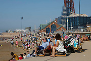 Domestic tourists enjoying the scorching hot weather on the beach, some with deck chairs, with the world famous Blackpool Tower in the background as temperatures in the country are expected to soar this week on 7th September, 2021 in Blackpool, United Kingdom. Temperatures in the UK are predicted to soar to highs of 29 degrees celsius, coinciding with a rise in daycation and staycation domestic tourism in the country as a result of Covid-19 precautions that make foreign travel increasingly costly and difficult.