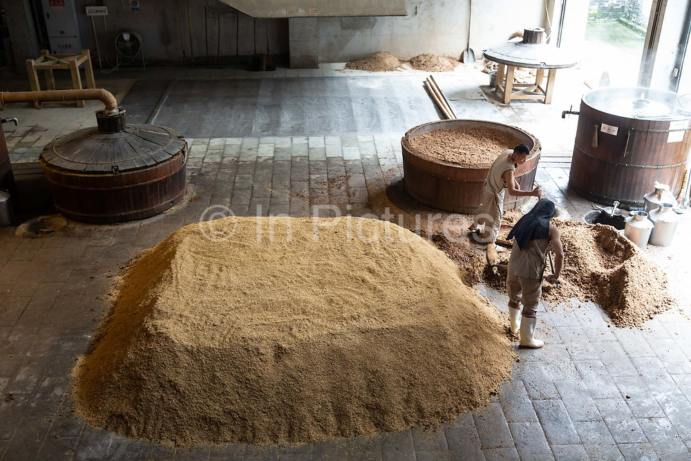 A worker fills a steam vat with fermented grain at a baijiu production facility that is part of the Shuijingfang museum, operated by Sichuan Swellfun Co., a unit of Diageo Plc in Chengdu, China, on Tuesday, Sept. 20, 2016. With less than 1 percent of baijiu, or white liquor, consumed abroad, Chinese distillers want to transform the fiery Chinese grain liquor into the new tequila for Americans and Europeans.