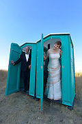 Wedding couple in adjacent portable toilets.