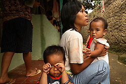 """Dian Dama Yanthi, 32, and her children, Galang, 3, and Gilang Rama, 1, are seen at their house in Tangerang, on the outskirts of Jakarta, Indonesia, April 19, 2006. Dian had an unsafe abortion and lost her best friend to an unsafe abortion. Both took the traditional medicine """"jamu."""" Dian also had a massage from a traditional birthing attendant. Over two million abortions are performed in Indonesia every year, many by unskilled practitioners. Thousands of women survive but often with life-long disabilities. It is said by doctors and activists that a woman dies every hour in Indonesia due to unsafe abortions."""