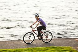 United States, Washington, Kirkland, woman bicylclng next to Lake Washington.  MR
